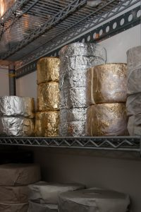 Cheeses stacked in a fridge
