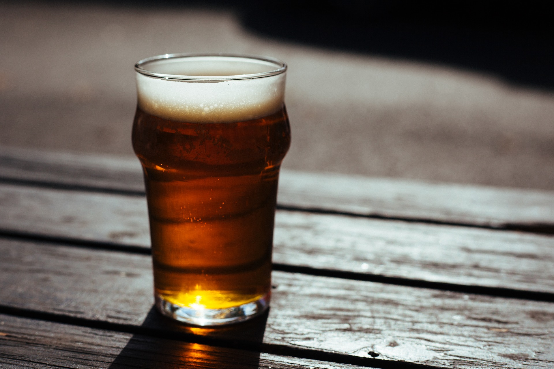 A pint of bitter on a wooden table in the sun
