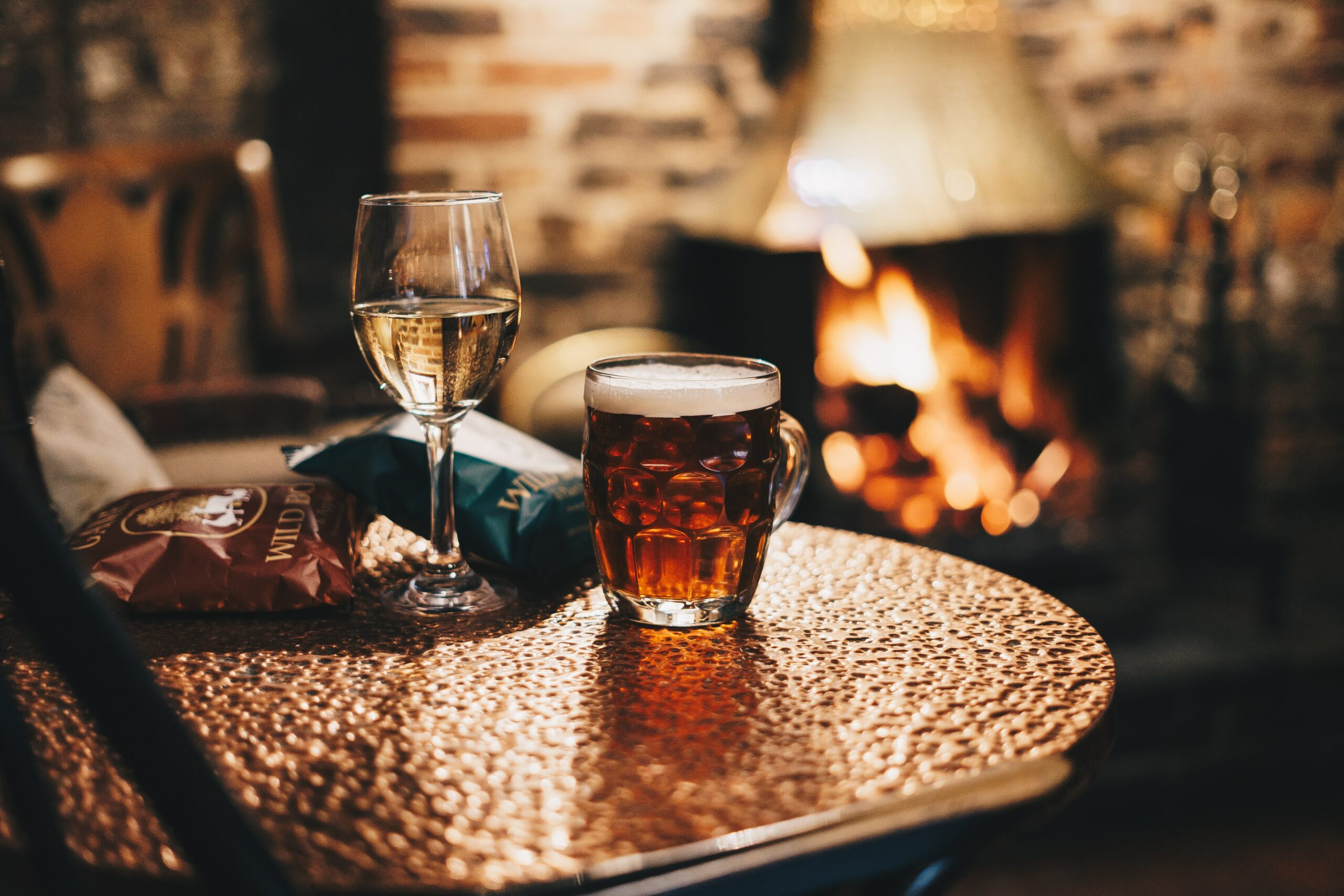 beer, wine and crisps on a pub table by an open fire