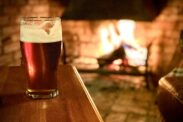 A pint of beer on a pub table by an open fire