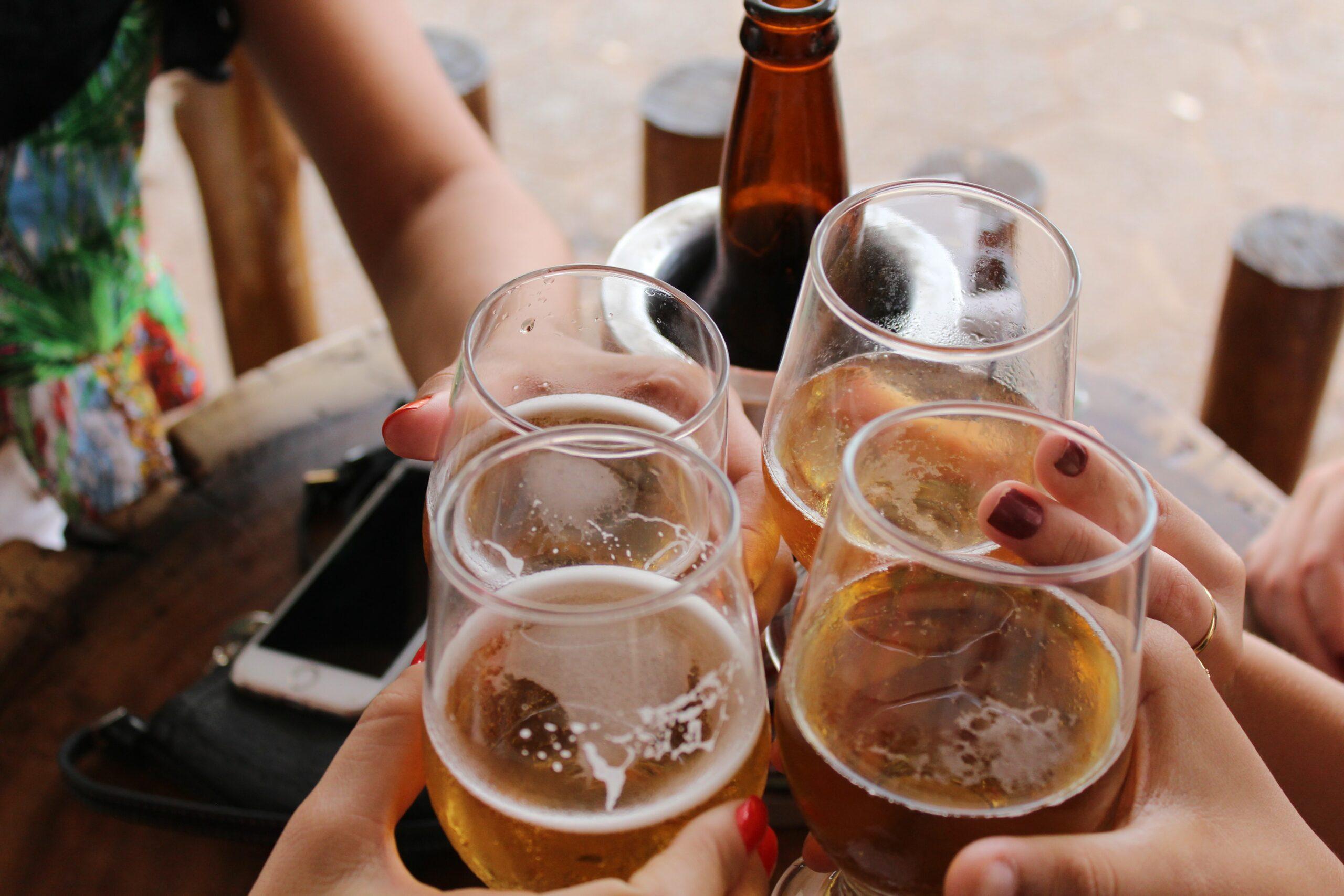 People holding beer glasses together